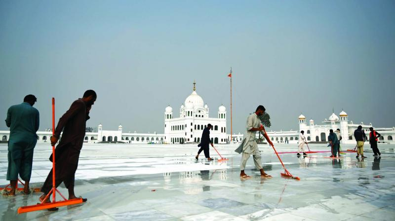 Workers clean the floor at Gurdwara Darbar Sahib in Kartarpur on Wednesday ahead of its opening. (Photo: AFP)