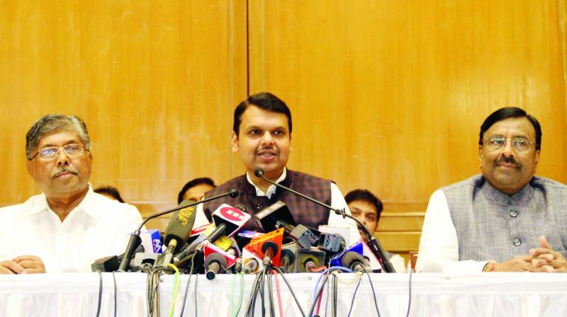 Devendra Fadnavis, flanked by Sudhir Mungantiwar and Chandrakant Patil, speaks at a press conference held on Friday. (Photo: AA)