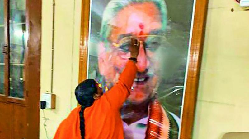 In memoriam Senior BJP leader Uma Bharti applies tilak on a photo of Vishwa Hindu Parishad leader late Ashok Singhal at the VHP office in New Delhi on Saturday. (Photo: PTI)