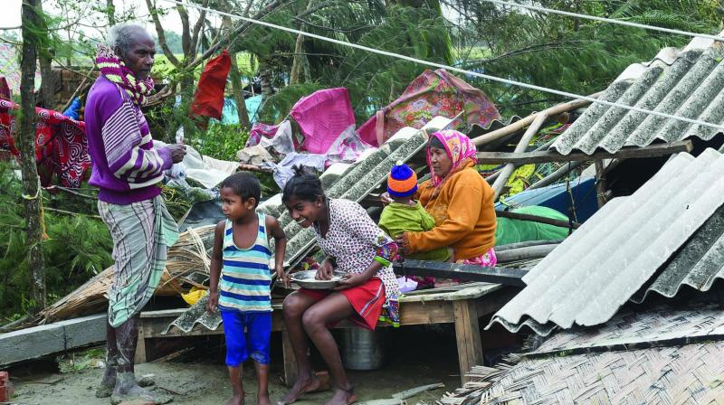 A family sits amongst the rubble of their house in the aftermath of cyclone Bulbul at Bakkhali in South 24 Parganas district of West Bengal on Sunday. (Photo: PTI)