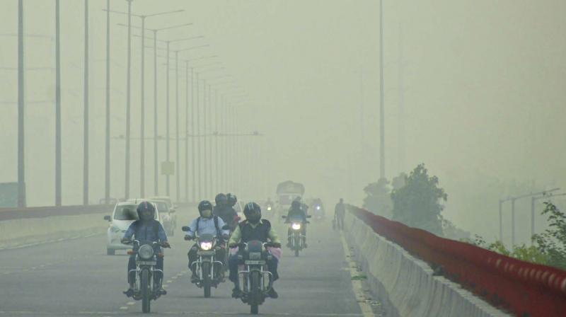 Commuters ride through heavy smog in Noida . (PTI)