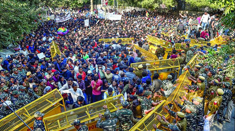Jawaharlal Nehru University students try to get past police barricades during a protest march towards Parliament in New Delhi on Monday. (Photo: PTI)