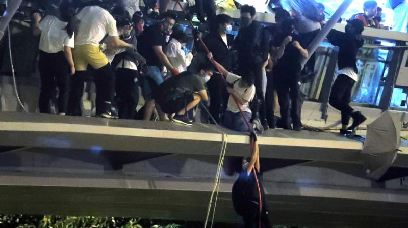 Dozens of Hong Kong pro-democracy protesters dramatically escaped a two-day police siege at a university campus late Monday by shimmying down ropes from a bridge to waiting motorbikes, after Beijing again warned it could intervene to end the crisis engulfing the city. (Photo: PTI)
