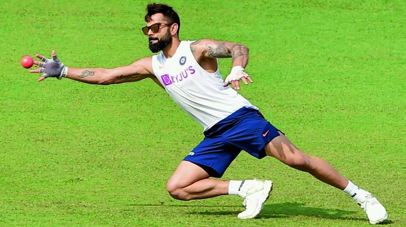 Virat Kohli goes for a catch during a training session on Thursday, the eve of the first pink-ball Day/Night Test match against Bangladesh at the Eden Gardens in Kolkata. (Photo: PTI)