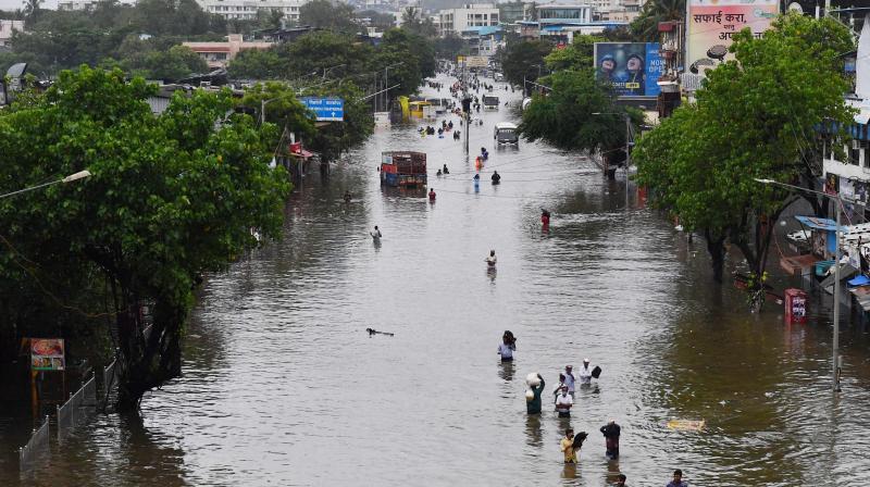 People wade along a waterlogged street following a heavy monsoon rainfall in Mumbai. (Photo: AFP)