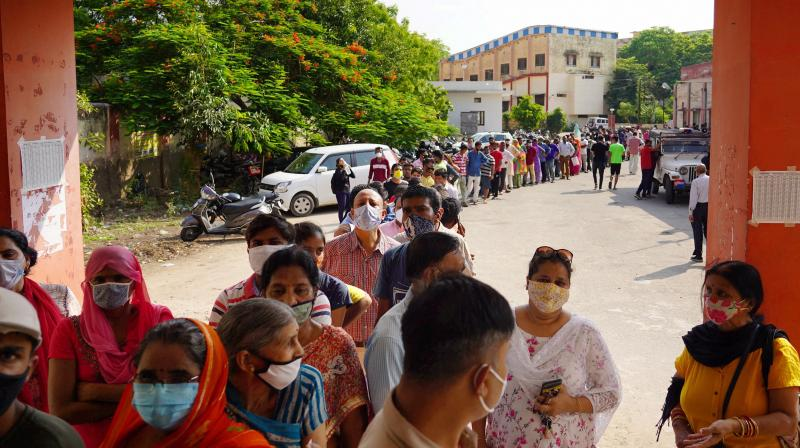 People wait to receive a dose of COVID-19 vaccine at a vaccination centre, in Ajmer. (PTI file photo)