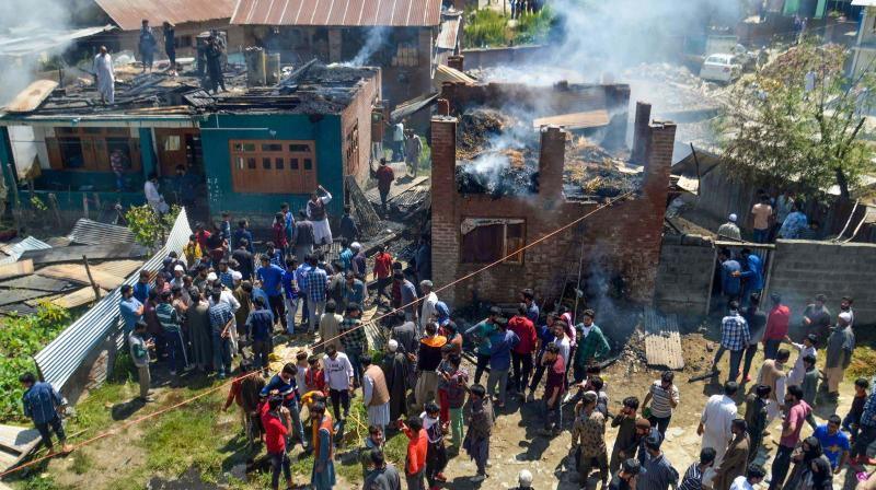 Local people gather outside the damaged houses where two top JeM militants were hiding during an encounter at Bijbehara area of Anantnag district on Tuesday. (Photo: PTI)