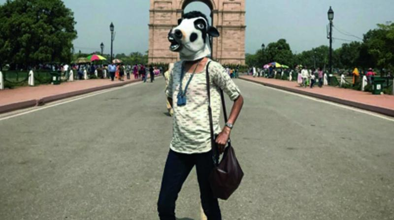 Photograph from Sujatro Ghosh's project shows women wearing a cow mask.