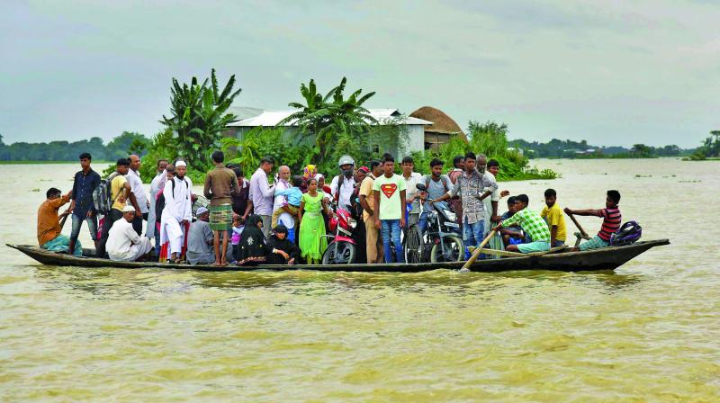 Flood affected villagers commute to safer places using a boat at Morigaon district in Assam. (Photo: AP/File)