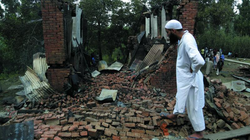 A Kashmiri Muslim villager looks at the debris of one of the damaged houses after a gunbattle at Bahmnoo village 58 km south of Srinagar, Kashmir recently. (Photo: AP)