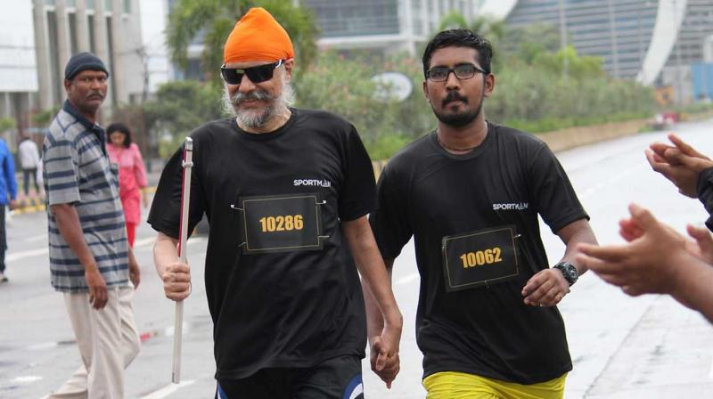 Amarjeet Chawla holds the hand of an escort as he approaches the finish line on one of his runs.