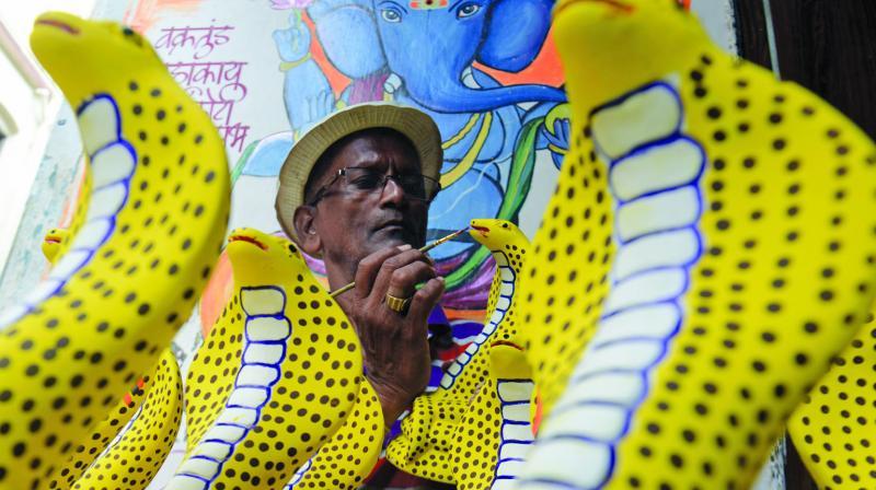 An artist prepares artificial snakes ahead of Nag Panchami. (Photo: Rajesh Jadhav)