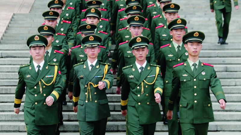 Chinese paramilitary policemen march outside the Great Hall of the People after attending a ceremony to commemorate the 90th anniversary of the founding of the People's Liberation Army in Beijing on August 1. (Photo: AP)