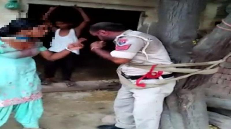 In a video, the policeman is seen tied to a tree and being beaten up severely by a woman who alleged that the policeman tried to rape her in an inebriated condition. (Photo: ANI)