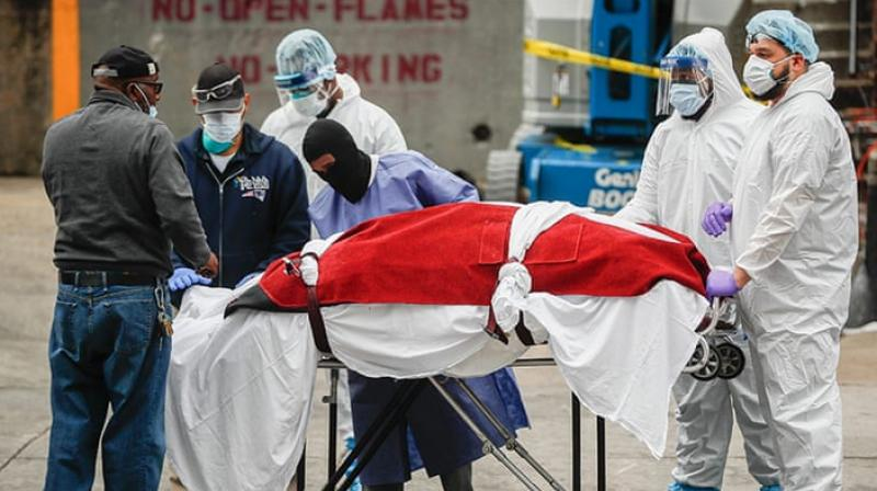 A body wrapped in plastic that was unloaded from a refrigerated truck is handled by medical workers wearing personal protective equipment at Brooklyn Hospital Center in New York City (AP Photo)