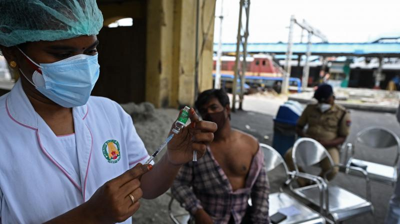 A health worker prepares to inoculate a man with a dose of the Covishield vaccine against the Covid-19 coronavirus at a vaccination camp organised at a railway station in Chennai. (Photo: AFP)