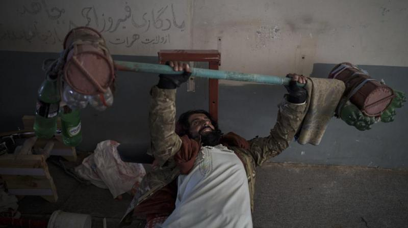 A Taliban fighter lifts a makeshift weight left behind by former prisoners at an empty area of the Pul-e-Charkhi prison in Kabul, Afghanistan. (Photo: AP)