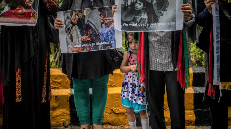 A young Afghan girls stands next to her mother participating with other Afghan women against Pakistan and the Taliban takeover of Afghanistan. (Photo: AP)