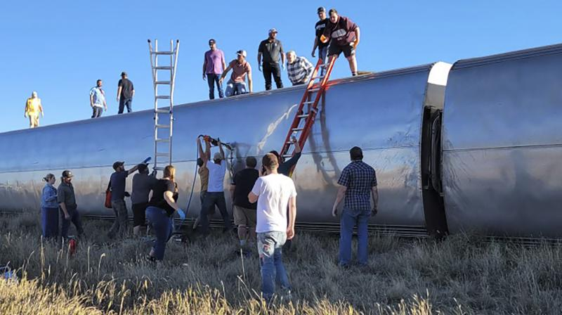 In this photo provided by Kimberly Fossen, people work at the scene of an Amtrak train derailment on Saturday, Sept. 25, 2021, in north-central Montana. (Photo: AP)