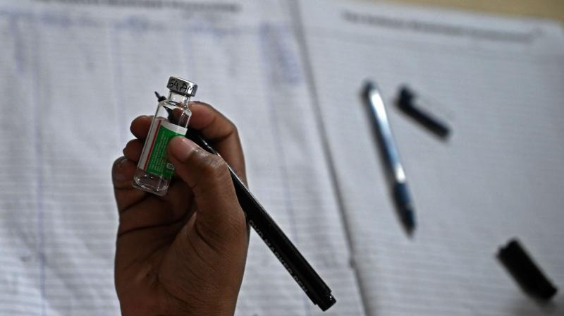 A health worker keeps the record of used vials of the Covishield vaccine against the Covid-19 coronavirus at a corporation health camp in Kolkata. (Photo: AFP)