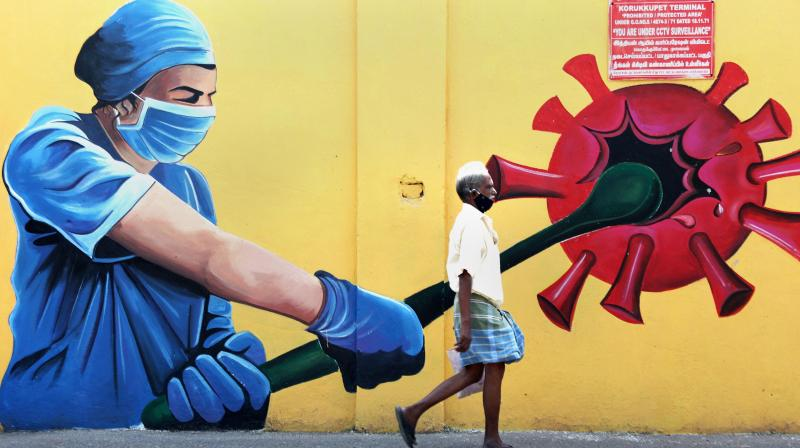 People walk past a wall mural on COVID awareness in Chennai. (Photo: PTI)