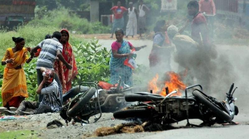 People injured in poll violence sit by the side of a road as a vehicle is set on fire by locals during Panchayat polls in Nadia district of West Bengal. (Photo: PTI)