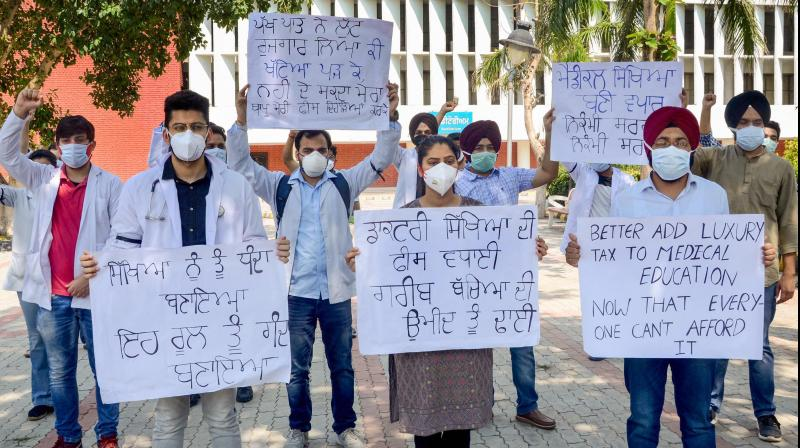Medical students hold placards to protest against fee hike. PTI photo