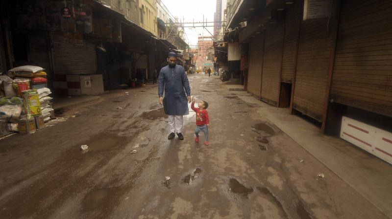 A man and his child walk on a deserted street in Old Delhi on Friday, March 27, 2020. A whole clutch of coronavirus positive cases are being traced to a religious event that took place in the Nizamuddin area of Delhi earlier this month. (DC Photo: Pritam Bandyopadhyay)