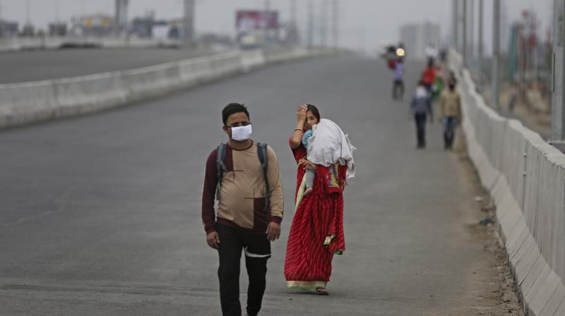 A couple carrying an infant walk along an expressway hoping to reach their home, hundreds of miles away, as New Delhi comes under lockdown. (AP)