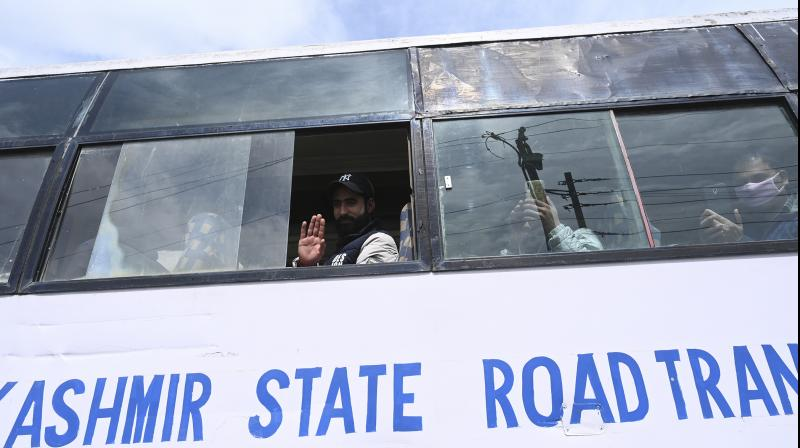 A man waves from inside a bus after he is discharged from a makeshift coronavirus quarantine facility set up at a hotel requisitioned for the purpose by the authorities in Srinagar, Jammu & Kashmir. Hundreds of local residents who were on their return from outside Kashmir were quarantined in such facilities. The authorities say that most of the 49 persons tested positive a have history of travel to various parts of India and abroad. (DC Photo: H U Naqash)