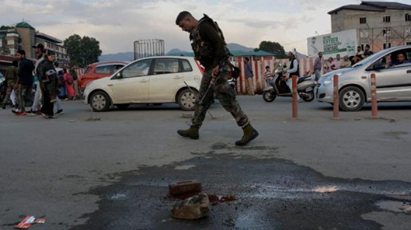 A security personnel looking for clues at the scene of a grenade blast by militants at Jehangir Chowk in Srinagar. (Photo: PTI)