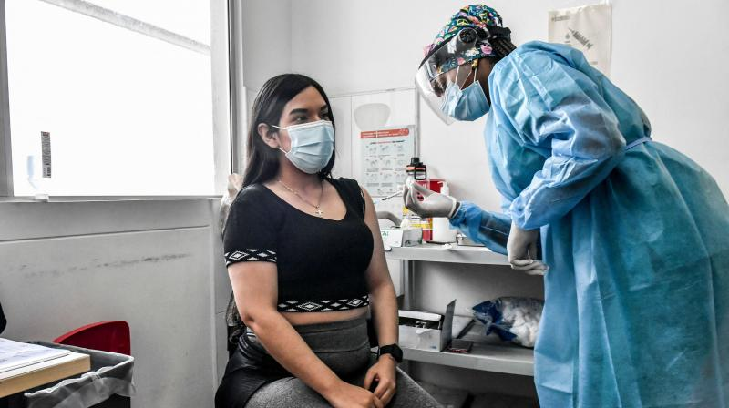 A pregnant woman is inoculated with the Pfizer-BioNTech vaccine against COVID-19 at a vaccination center in Medellin, Colombia on July 24, 2021. (JOAQUIN SARMIENTO / AFP)