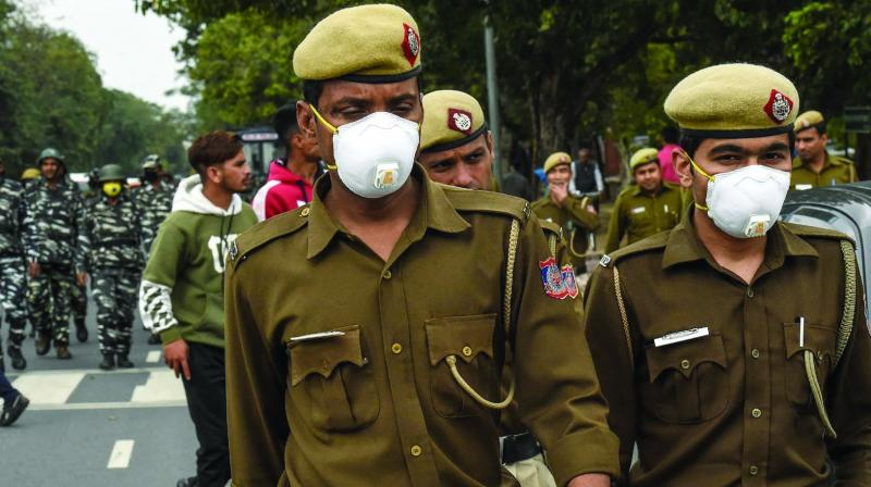 Security personnel wear masks as they patrol on a road in New Delhi on Friday. (Photo: AFP)