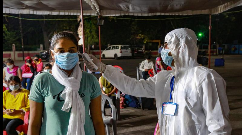 A medic checks the temperature of a stranded student from Kota upon her arrival, during the nationwide lockdown to curb the spread of coronavirus, in Indore. PTI Photo