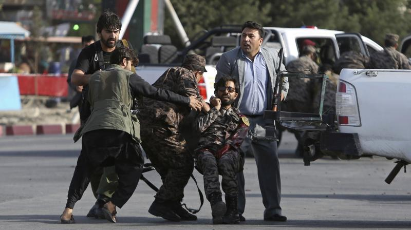Afghan security personnel carry an injured comrade after an attack near the Kabul International Airport, in Kabul, Afghanistan, Sunday. (Photo: AP)