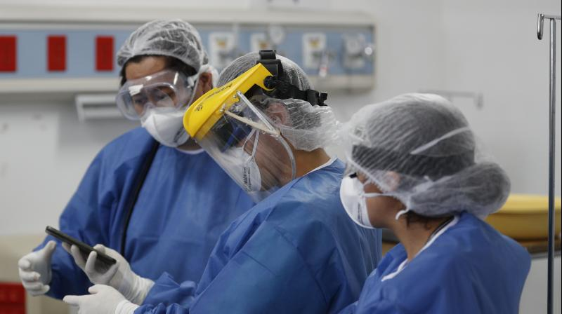 Medical staff wearing full protective gear talk about a patient in the COVID-19 ward at the Hospital Juarez, in Mexico City. AP Photo