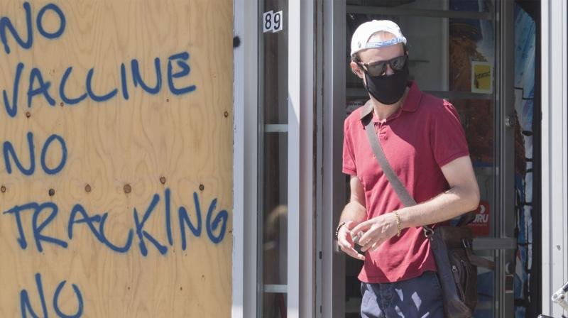 A man wears a face mask as he passes by graffiti reading 'No vaccine, No tracking, No COVID'. (AP)