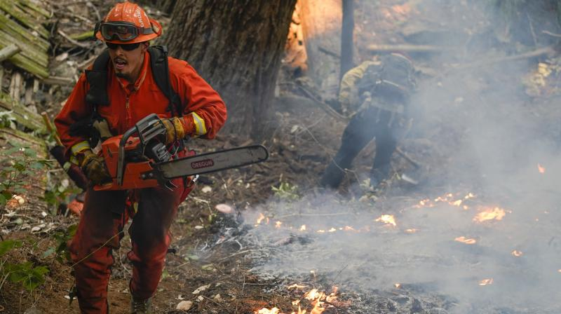 A member of a California Dept. of Corrections fire crew runs along a containment line with a chainsaw while fighting the CZU August Lightning Complex Fire. (AP)