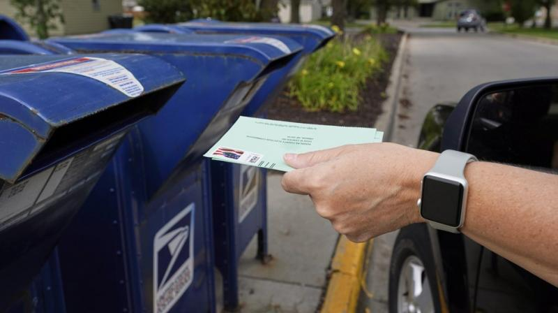 A person drops applications for mail-in-ballots into a mail box in Omaha. (AP File Image)