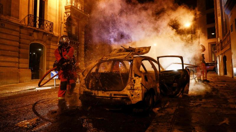 Firefighters extinguish a burning car near the Champs-Elysees in Paris on August 23, 2020, as PSG supporters riot after the UEFA Champions League final football match between Paris Saint-Germain and Bayern Munich at the Luz stadium in Lisbon. (AFP)