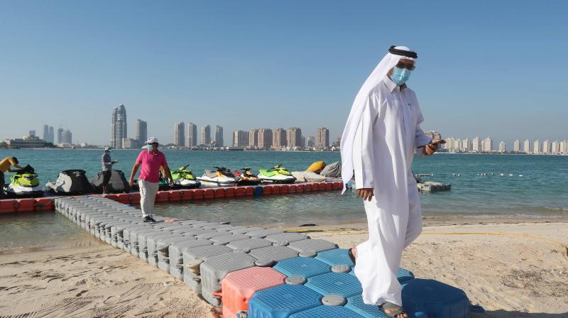 Men wearing protective masks walk on a plastic pier at Katara beach in the Qatari capital Doha. (AFP)