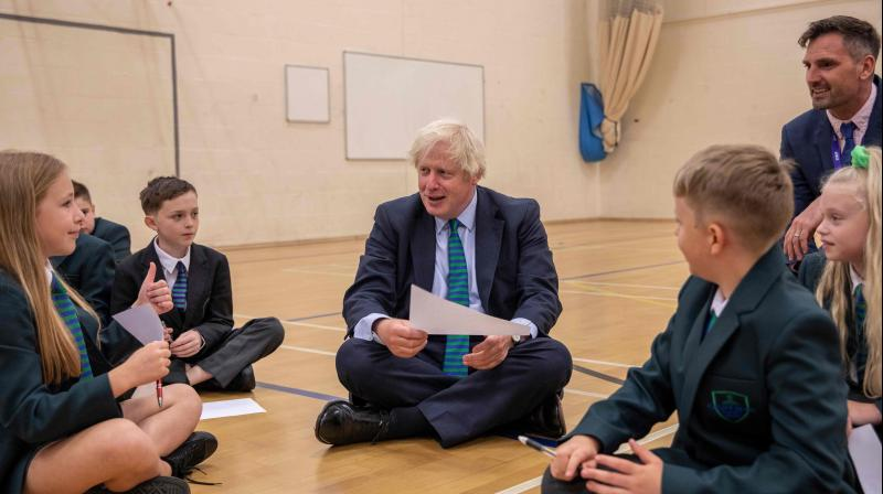 Britain's Prime Minister Boris Johnson (C) takes part in an induction session in the gymnasium with year sevens as he visits Castle Rock school, Coalville, central England. (AFP)