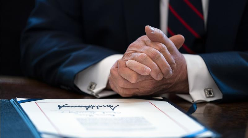 US president Donald Trump signed the coronavirus stimulus relief package at the White House on March 27, 2020, in Washington. (AP)