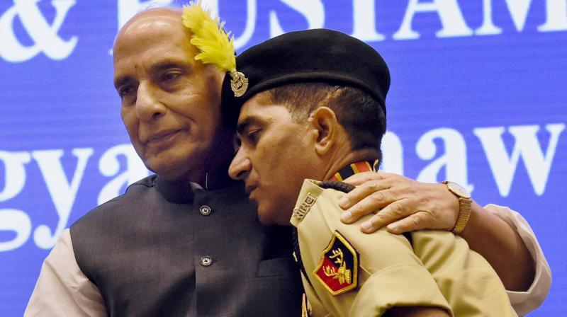 Union Home Minister Rajnath Singh after presenting Police Medal to constable Godhraj Meena, who took on militants when they attacked a BSF bus in Udhampur in J&K on August 5, 2015, at the 15th BSF investiture ceremony in New Delhi. (Photo: PTI)