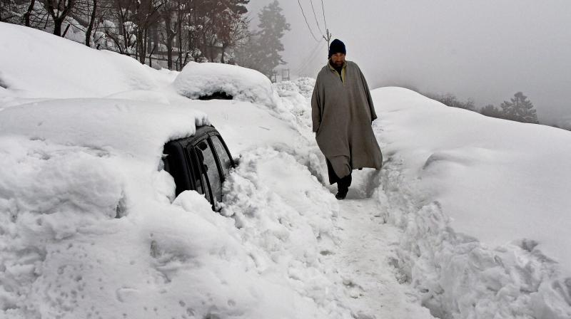 A villager walks near a vehicle coverd with snow on Srinagar-Gulmarg Road after heavy snowfall at Tangmarg in Baramulla District of North Kashmir. (Photo: AP)