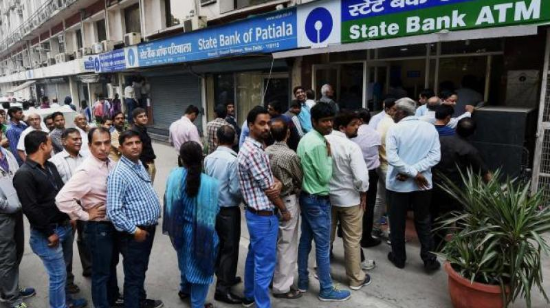 People queue up outside an ATM to withdraw money in New Delhi. (Photo:PTI)