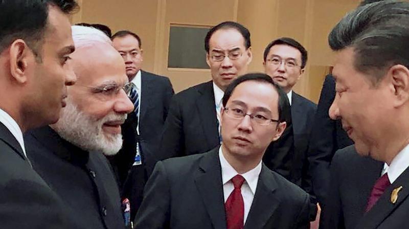Prime Minister Narendra Modi and Chinese President Xi Jinping exchange greetings at the BRICS leaders' informal gathering, in Hamburg. (Photo: AP)