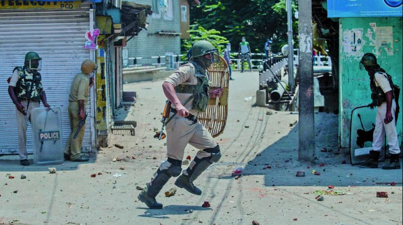 An Indian paramilitary soldier runs for cover as Kashmiri protesters pelt stones at him during a protest in Srinagar on Saturday. (Photo: AP)