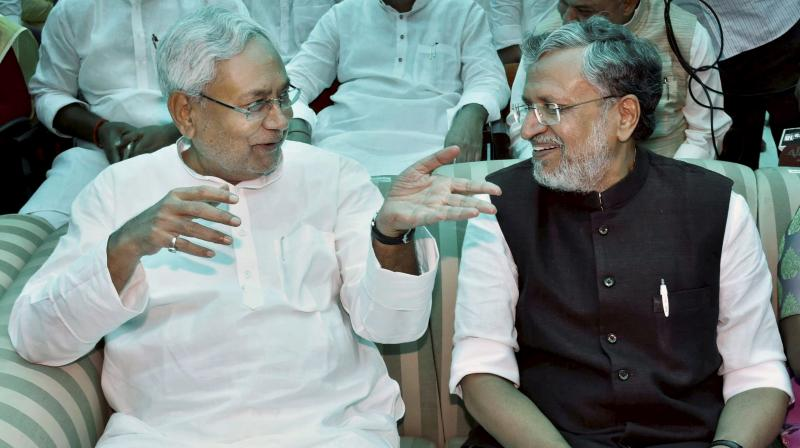 Nitish Kumar with senior BJP leader Sushil Kumar Modi at an oath taking ceremony, at Raj Bhawan in Patna. (Photo: AP/File)