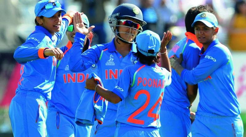 The Indian team celebrates the fall of a wicket.